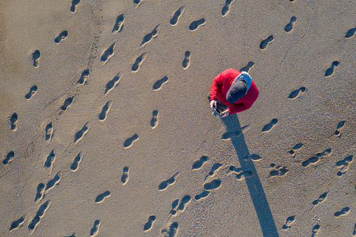 Aerial view of man piloting a drone on tropical beach