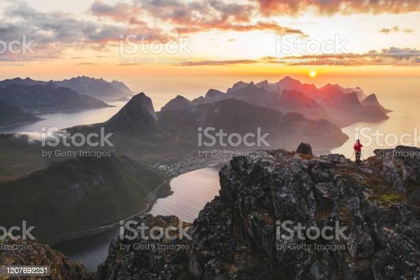 Photo of Aerial view of man  standing on mountain peak on Senja island