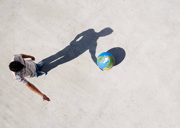 aerial view of man with shadow and globe - illusion stock photos and pictures