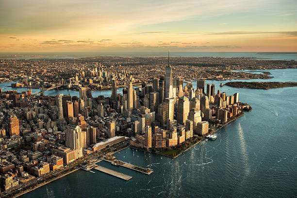 Aerial view of Manhattan island Helicopter point of view of Manhattan island in New York City at sunset. manhattan financial district stock pictures, royalty-free photos & images