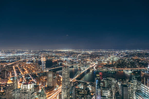 aerial view of manhattan skyline at night - urban sprawl stock photos and pictures
