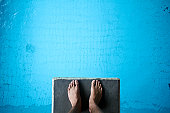 Aerial view of man's feet on diving board on blue
