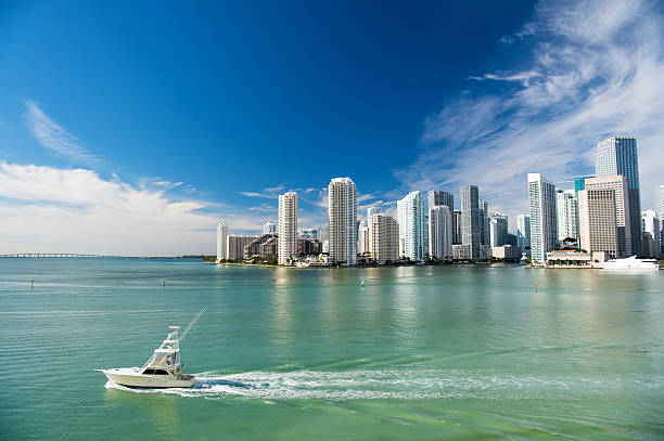 Aerial view of Miami skyscrapers with blue sky, boat sail Aerial view of Miami skyscrapers with blue cloudy sky,white boat sailing next to Miami downtown miami beach stock pictures, royalty-free photos & images