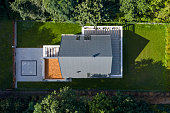 Aerial view from drone of modern house with green lawn surrounded by trees