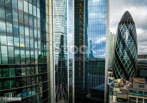 Color image depicting an aerial view of the modern futuristic architecture and massive urban sprawl of the city of London, UK. The image is full of glass and steel skyscrapers, including the Gherkin (30 St Mary Axe).