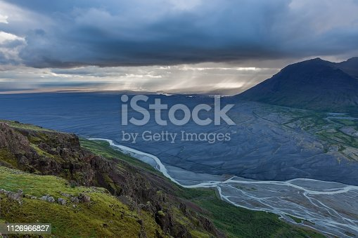 Aerial view of moraine glacier river in South Iceland. Dead black volcanic desert stretching to horizon. Heavy clouds and rain shower pouring far away.
