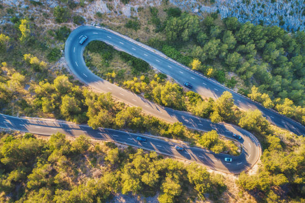 Luftaufnahme der Kurve Bergstraße mit Autos, grünen Wald bei Sonnenuntergang im Sommer in Europa. Landschaft mit Asphaltstraße, Bäume auf den Felsen. Autobahn durch den Park. Draufsicht von fliegenden Drohne. Natur – Foto