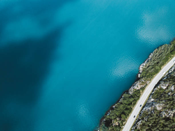 Aerial view of mountain road above turquoise lake in Norway stock photo