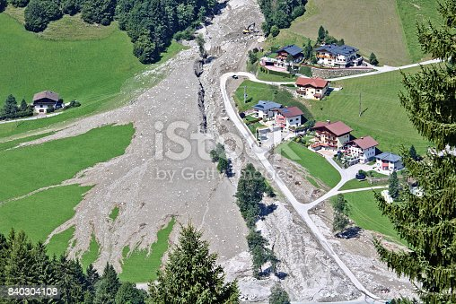 Aerial view of mountain stream in the Austrian Alps blocked after a massive mudflow with excavator and truck working to clean up and small village nearby
