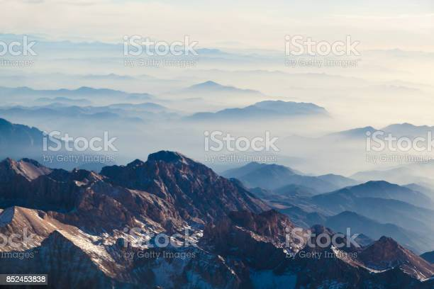 Photo of Aerial view of mountains and clouds through airplane window