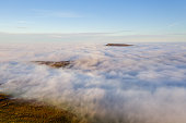 Aerial view of mountains rising above a sea of fog on a bright, sunny day.