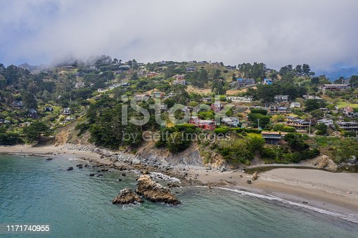 An aerial view of Muri Beach with gentle waves, rock formations and  whispy fog rolling over the hillside dotted with luxury homes.
