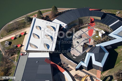 Canberra, Australia - August 18, 2009: aerial view of museum around a lake, few people walking around enjoying the sunny day