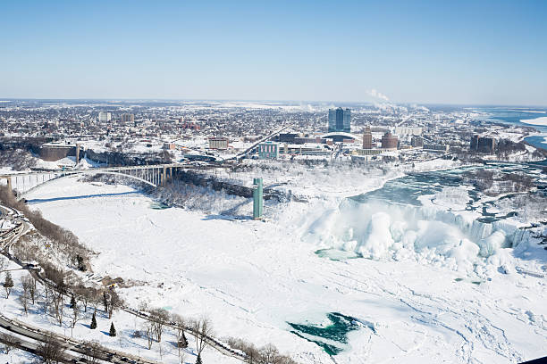 Aerial View of Niagara Falls Aerial View of Niagara Falls from the Canadian side looking at the frozen American waterfalls, Rainbow bridge and the city of Niagara Falls, New York rainbow bridge ontario stock pictures, royalty-free photos & images