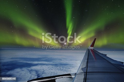istock Aerial view of Northern Lights (Aurora Borealis) from window of an flying airplane 666969046