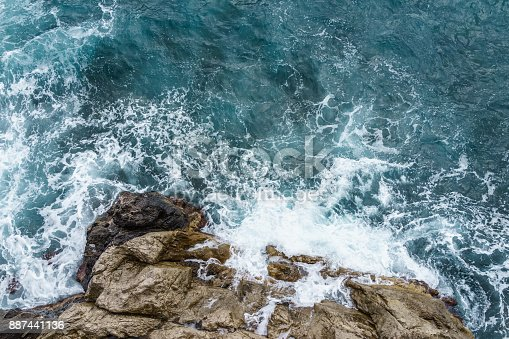istock Aerial view of ocean wave crashing on rocky cliff with white spray and foam on deep blue sea water after storm 887441136