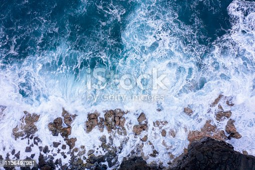 Aerial view of ocean waves breaking on rocky beach