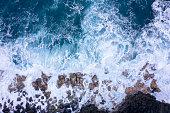 Aerial view of ocean waves breaking on rocky beach