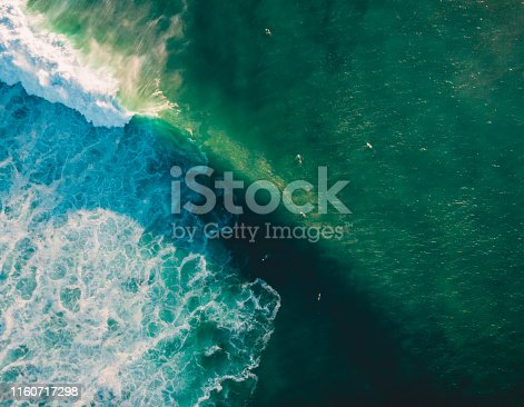 843079528istockphoto Aerial view of ocean with wave and surfers. Big barrel wave 1160717298