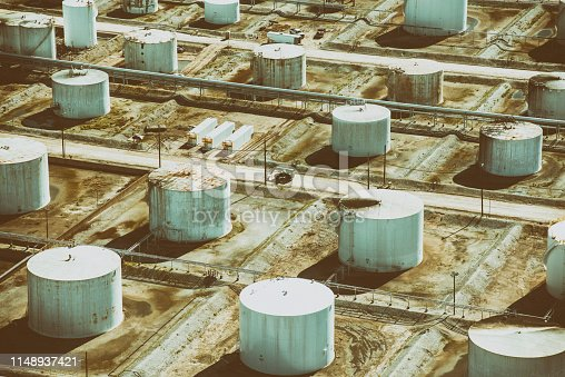 Directly above a group of storage tanks which appear rusted and old at an oil refinery in Texas City, Texas, located just south of Houston on Galveston Bay.