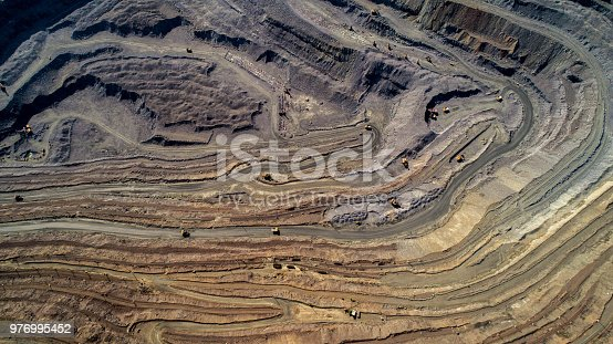 istock Aerial view of opencast mining quarry with lots of machinery at work. 976995452