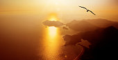 Aerial View of orange color seascape and flying seagulls during sunset in Fethiye, Turkey