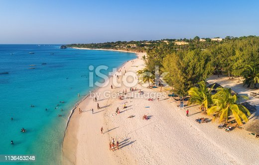 1136453253 istock photo Aerial view of palms on the sandy beach of Indian Ocean at sunset. Summer holiday in Zanzibar, Africa. Tropical landscape with palm trees, white sand, clear blue water with waves. Top view. Seascape 1136453248