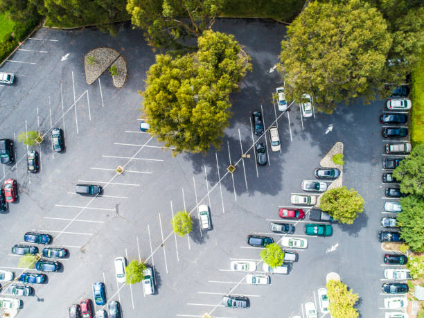 Aerial view of parking area. This picture shows a parking area surrounded by greenery.There are some cars. parking lot stock pictures, royalty-free photos & images