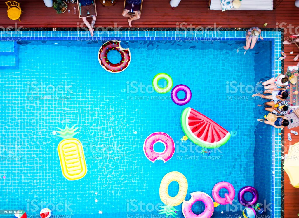 Aerial view of people enjoying the pool with inflatable tubes stock photo