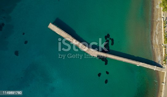 a close up on cute baby who is standing on a wooden fence outside on a summer day, hanging over the edge and looking down into the water below.