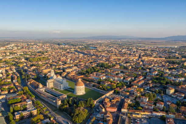 Aerial View of Pisa & Leaning Tower The Campo dei Miracoli ('Field of Miracles') is a wide, walled area at the heart of the city of Pisa, Tuscany, Italy, recognized as one of the main centers for medieval art in the world. Partly paved and partly grassed, it is dominated by four great religious edifices: the Duomo, the Leaning Tower (the cathedral's campanile), the Baptistery and the Camposanto. It is otherwise known as Piazza del Duomo ('Cathedral Square'). In 1987 the whole square was declared a UNESCO World Heritage Site. The heart of the Campo dei Miracoli is the Duomo, the medieval cathedral, entitled to St. Mary. The facade, of grey marble and white stone set with discs of coloured marble, was built by a master Rainaldo. pisa stock pictures, royalty-free photos & images