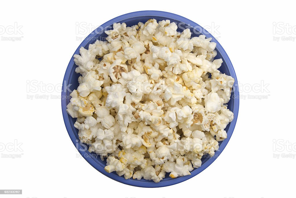 Aerial view of popped popcorn in a blue bowl on white table stock photo