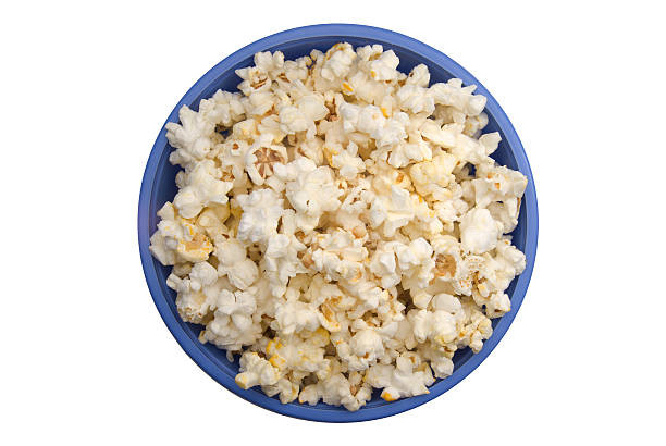 Aerial view of popped popcorn in a blue bowl on white table