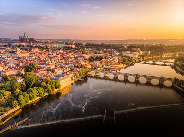 aerial view of prague castle, cathedral and charles bridge at sunrise in prague - чехия стоковые фото и изображения
