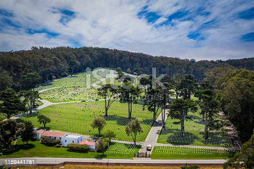 An aerial view of the Presidio National Cemetary in San Francisco California. Cross tombstones fill the green lawn.