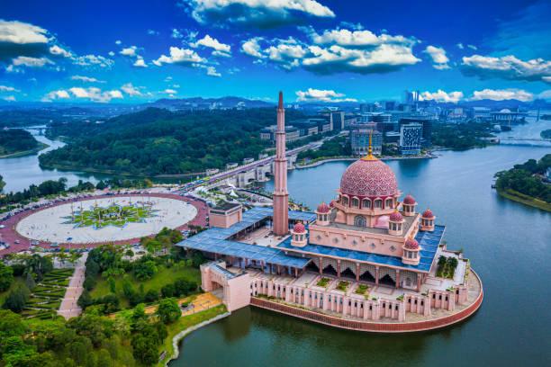 vista aérea da mesquita putra com o centro da cidade de putrajaya com lago ao pôr do sol em putrajaya, malásia. - malásia - fotografias e filmes do acervo