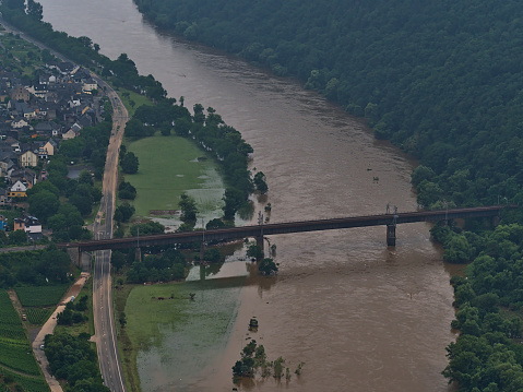 Aerial view of railway bridge crossing Moselle river near village Ediger-Eller, Rhineland-Palatinate, Germany with flooded riverbank and high water level.