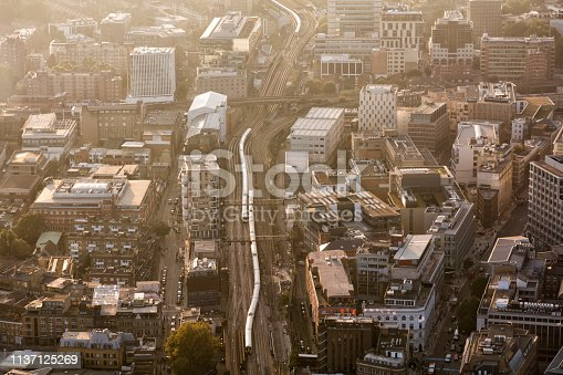 Aerial view of railway with trains, train driving to the London Bridge Station, back lit, orange and bronze colors, City of London, horizontal orientation, United Kingdom.