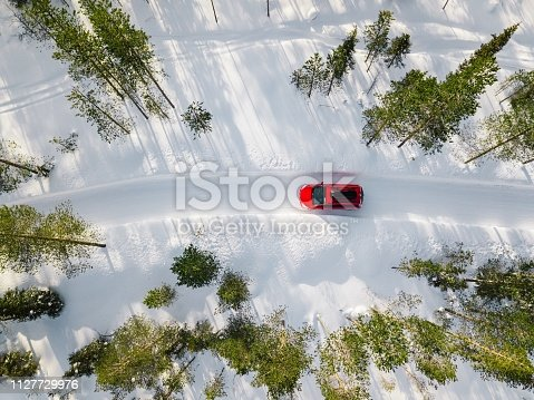 istock Aerial view of red car driving through the white snow winter forest on country road in Finland, Lapland. 1127729976