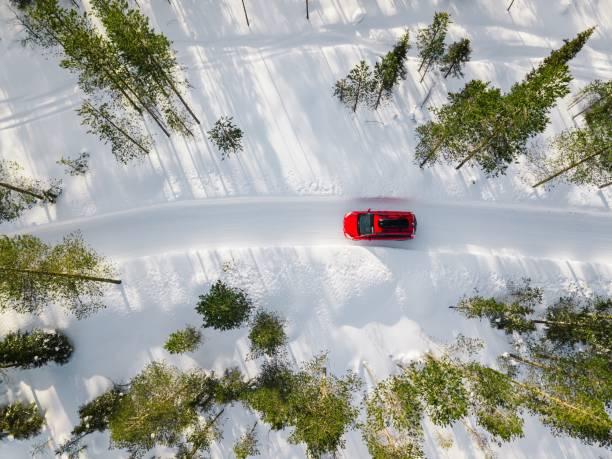 Luftaufnahme des roten Auto fahren durch den weißen Schnee Winterwald auf Landstraße in Finnland, Lappland. – Foto