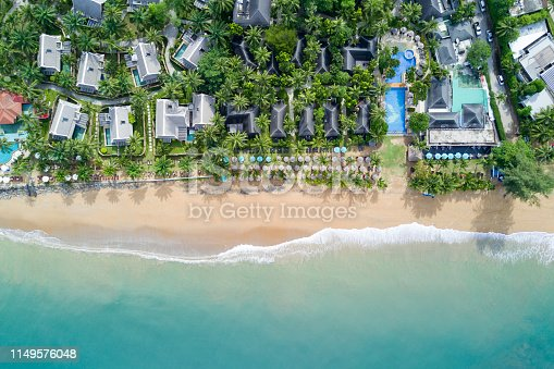 Aerial view of resort villa layout with coconut trees, umbrellas and deck chairs on the beach. Ocean wave reaching coastline. Beautiful tropical beach from top view. Andaman sea in Thailand. Summer holiday concept