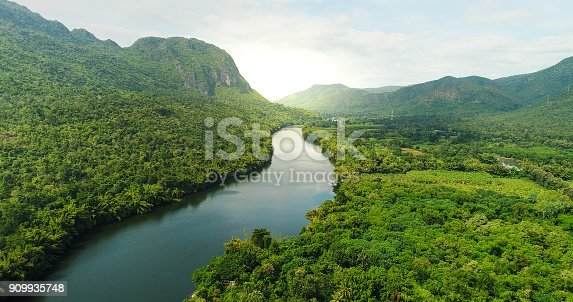 istock Aerial view of river in tropical green forest with mountains in background 909935748