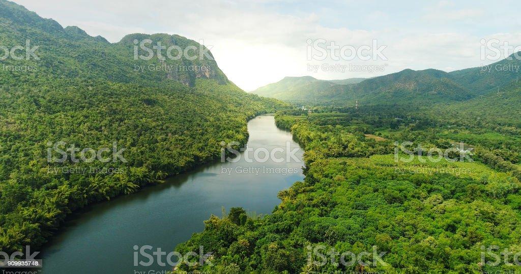 Luftaufnahme des Flusses in tropischen grünen Wald mit Bergen im Hintergrund – Foto
