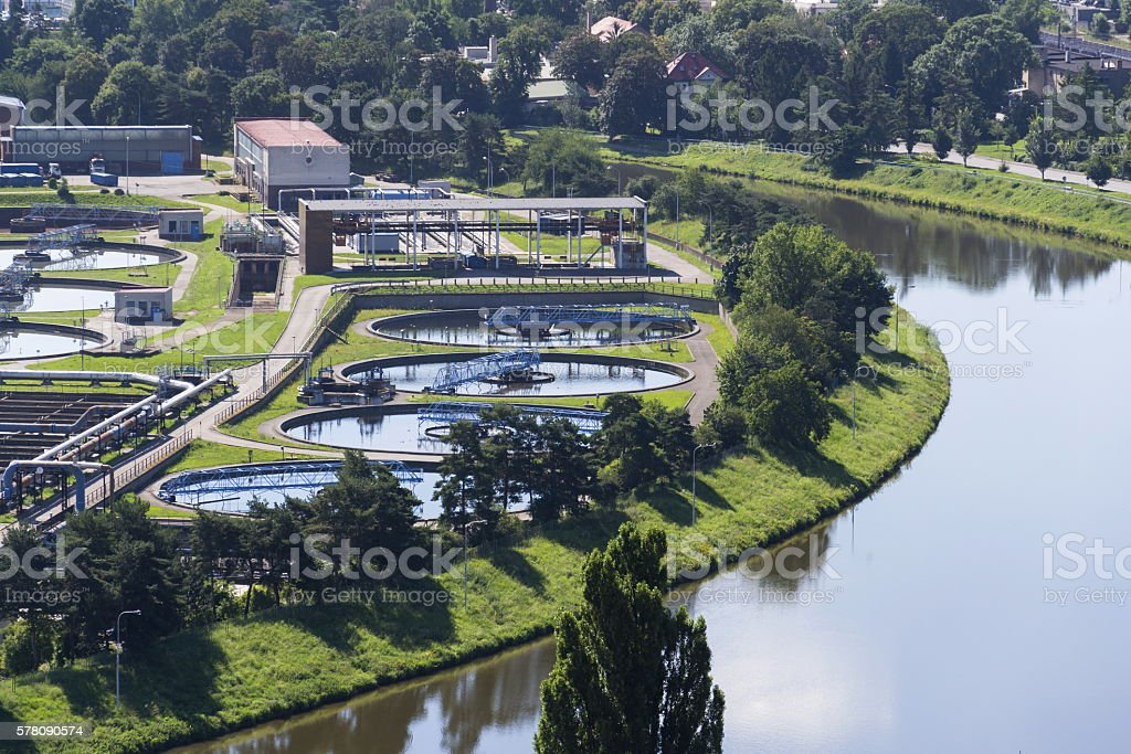 Aerial view of river meandering around sewage water treatment plant stock photo