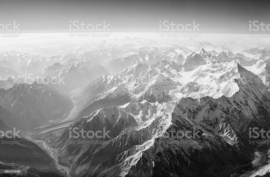 Aerial View of River Winding Through Foggy Himalyan Mountains stock photo