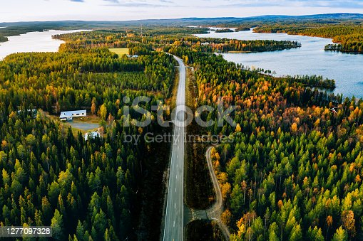 istock Aerial view of road and forest in autumn colors with blue water lake. 1277097328