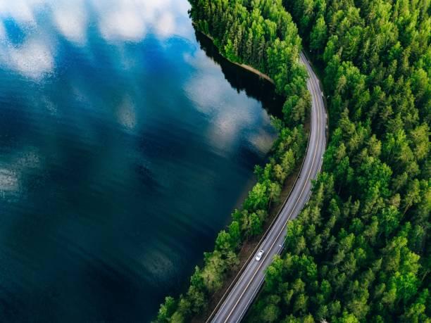 Luftaufnahme der Straße zwischen grünem Wald und blauem See in Finnland – Foto