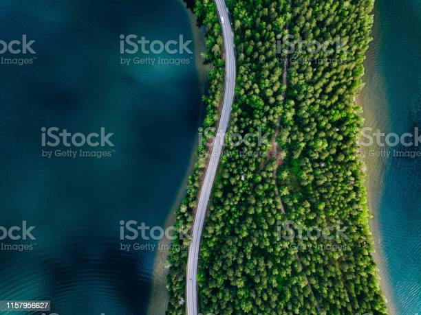 Photo of Aerial view of road between green forest and blue lake in Finland