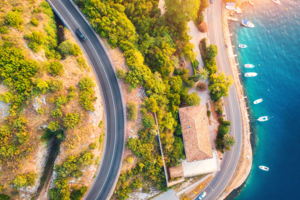 Aerial view of road, boats and yachts in water, buildings at sunset in summer. Colorful landscape with roadway, sea coast, port, green trees in spring. View from above of highway in Croatia. Travel stock photo