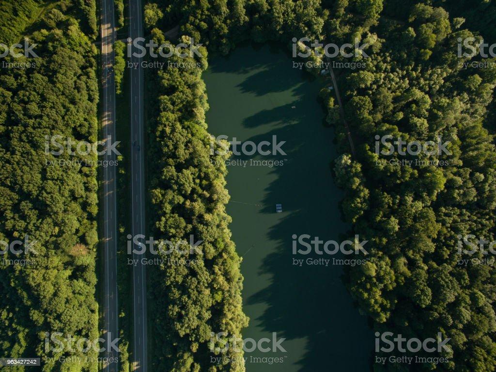 aerial view of road in beautiful forest with blue lake - Zbiór zdjęć royalty-free (Bez ludzi)